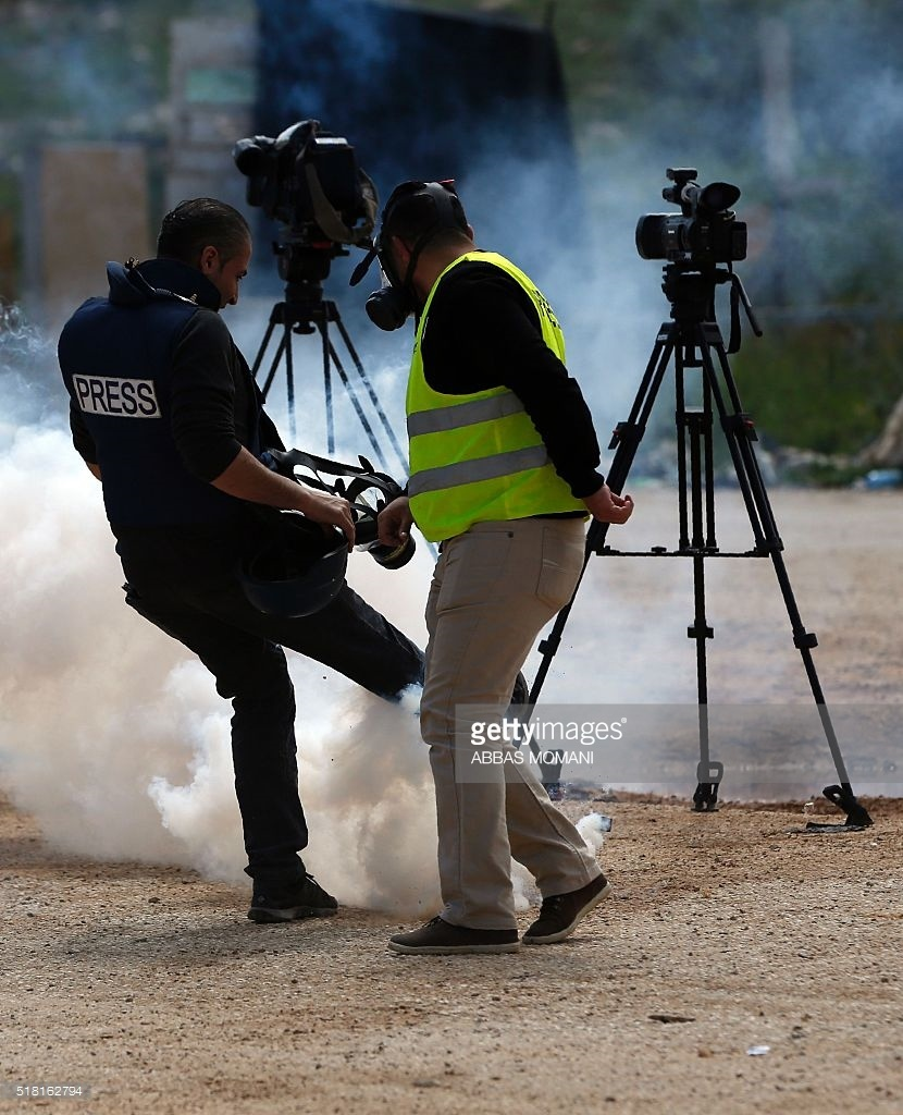A Palestinian journalist kicks a tear gas canister fired by Israeli security forces as they cover a demonstration by Palestinian protesters