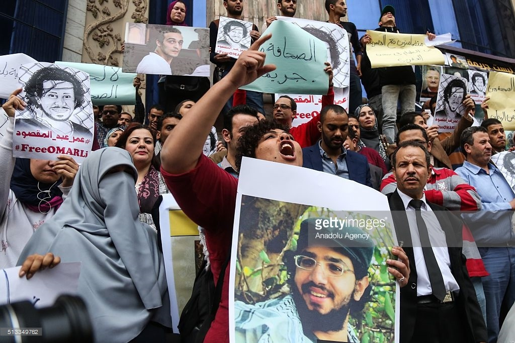 Journalists hold posters and chant slogans during a protest in Cairo