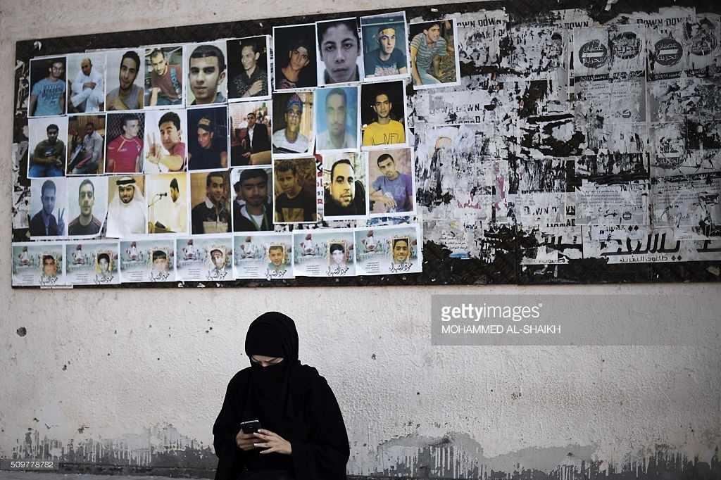 A Bahraini woman sits near portraits of jailed political activists and protesters killed during clashes with police,